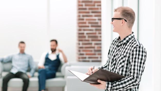 Lächelnder mitarbeiter mit einer zwischenablage, die im büro steht. foto mit kopienraum