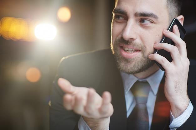 Lächelnder moderner geschäftsmann talking by smartphone