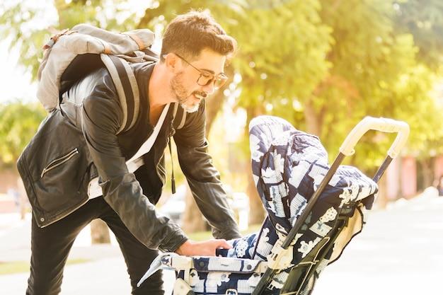 Lächelnder moderner mann mit seinem rucksack, der um seinem baby im park sich kümmert