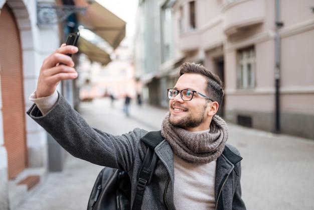 Lächelnder modischer junger mann, der selfie in der winterstadt nimmt.