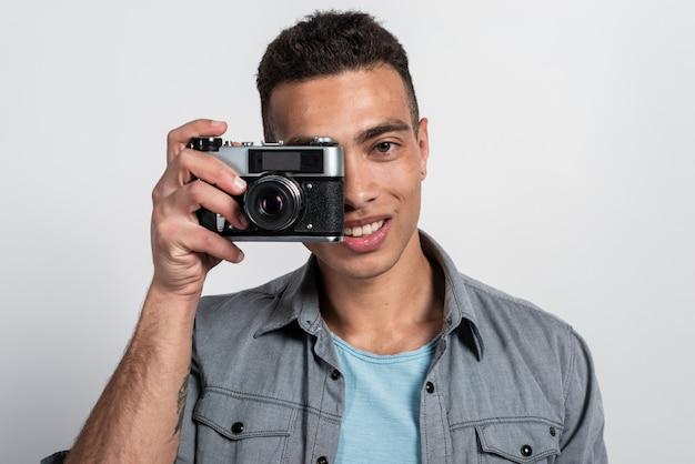 Lächelnder mulattemann, der ein retro- photocamera gegen sein gesicht hält und die kamera betrachtet