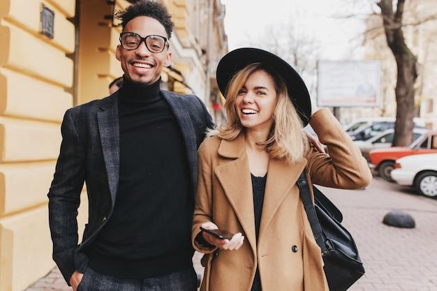 Lächelnder mulattentyp im schwarzen hemd, das mit seiner bezaubernden europäischen freundin aufwirft. porträt im freien des lachenden blonden mädchens mit telefon, das nahe afrikanischem jungem mann steht.