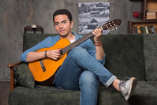 Lächelnder musiker, der gitarre spielt und auf dem sofa sitzt. hochwertiges foto