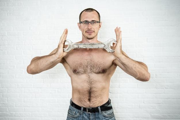Lächelnder muskulöser arbeiter mann mit großem schraubenschlüssel in den händen
