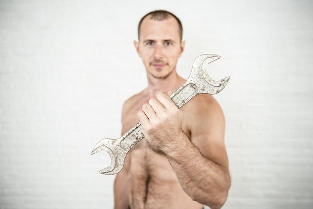 Lächelnder muskulöser arbeiter mann mit großem schraubenschlüssel in der hand
