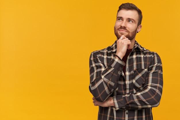 Lächelnder nachdenklicher junger mann im karierten hemd mit bart, der träumt und zur seite über gelbe wand schaut. sieht inspiriert aus