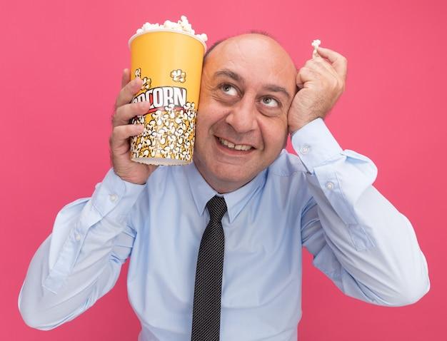 Lächelnder nachschlagender mann mittleren alters, der weißes t-shirt mit krawatte hält eimer popcorn mit popcornstück um gesicht lokalisiert auf rosa wand trägt