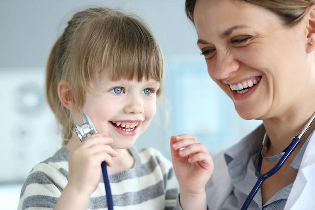 Lächelnder netter kleiner patient, der auf ärztin einwirkt