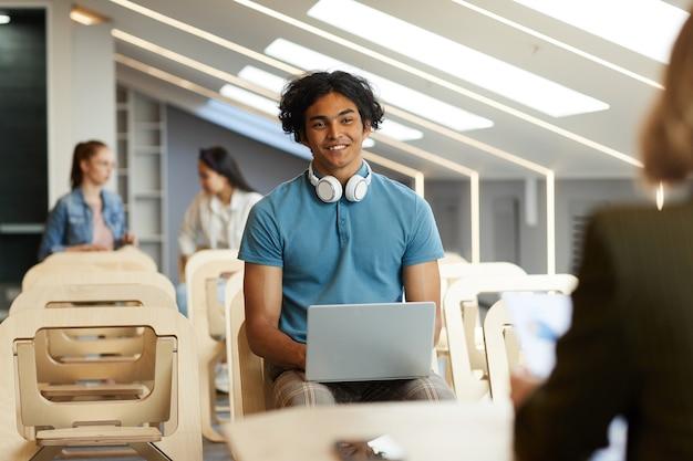 Lächelnder neugieriger gemischter rassenmann mit kabellosen kopfhörern um den hals, der mit laptop auf stuhl sitzt und mit universitätslehrer spricht