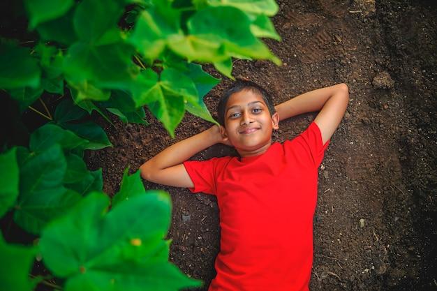 Lächelnder niedlicher indischer junge, der auf boden liegt