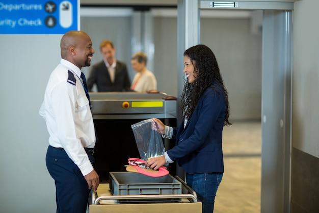 Lächelnder pendler, der mit dem sicherheitsbeamten des flughafens interagiert, während er zubehör aus der kiste sammelt