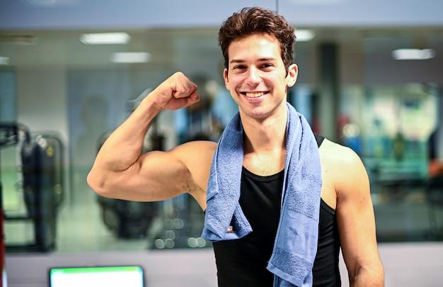 Lächelnder personal trainer im fitnessstudio zeigt seinen bizeps