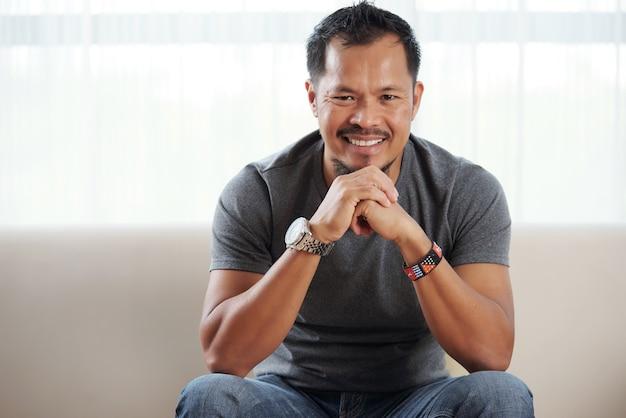 Lächelnder philippinischer mann, der mit dem kinn auf gefalteten händen, gegen helles fenster sitzt