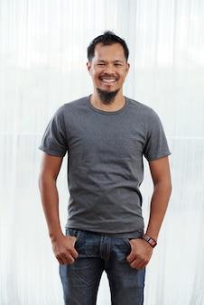 Lächelnder philippinischer mann, der mit den daumen in den taschen vor hell beleuchtetem fenster steht