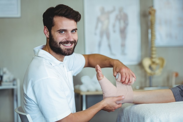 Lächelnder physiotherapeut, der den verletzten füßen des patienten einen verband anlegt