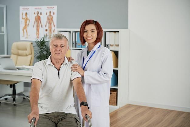 Lächelnder physiotherapeut und älterer patient, der nach der ersten rehabilitationssitzung im rollstuhl sitzt