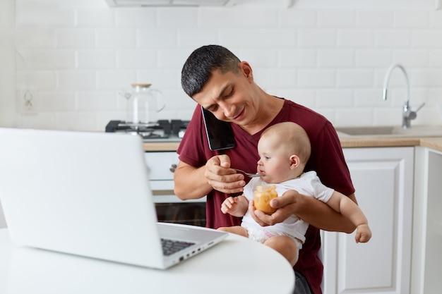 Lächelnder positiver mann mit kastanienbraunem, lässigem t-shirt, der telefon spricht, während er kleine tochter oder sohn mit fruchtpüree füttert und am tisch in der küche vor dem notebook sitzt.