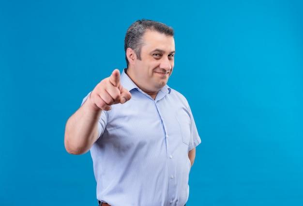 Lächelnder positiver mann mittleren alters, der blaues gestreiftes hemd zeigt zeigefinger auf kamera auf blauem hintergrund zeigt