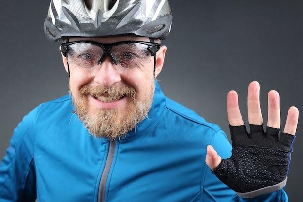 Lächelnder radfahrer winkt mit der hand
