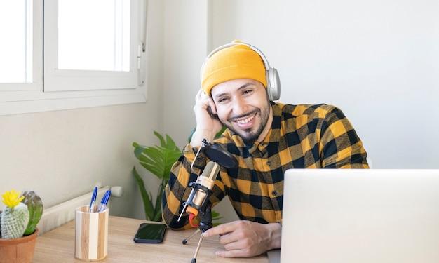 Lächelnder radiomoderator, der mit mikrofon im büro sitzt