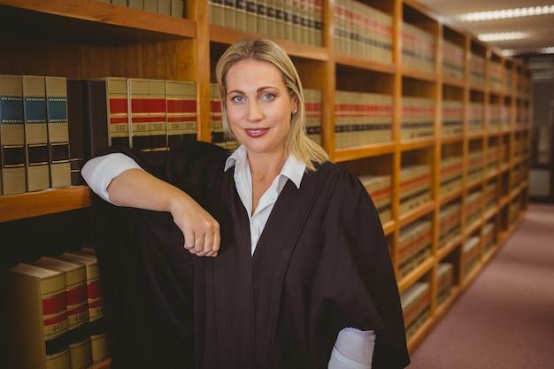 Lächelnder rechtsanwalt, der auf regal sich lehnt
