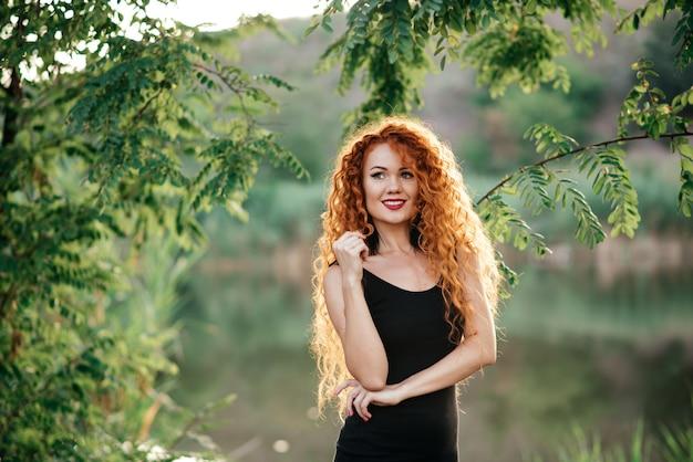 Lächelnder redhead draußen hintergrundbeleuchtet durch sonne, modetrieb.