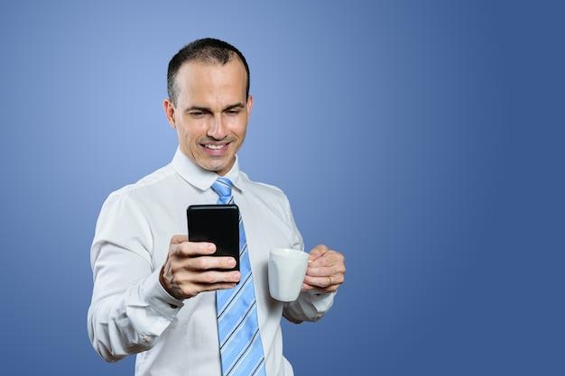 Lächelnder reifer brasilianischer mann in der formellen kleidung, die ein smartphone und eine tasse hält. blauer hintergrund.