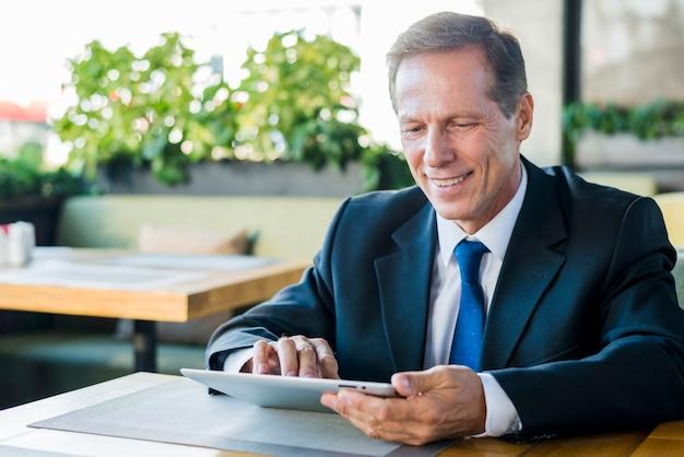 Lächelnder reifer geschäftsmann, der an digitaler tablette im restaurant arbeitet