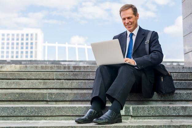 Lächelnder reifer geschäftsmann, der auf dem treppenhaus arbeitet an laptop sitzt