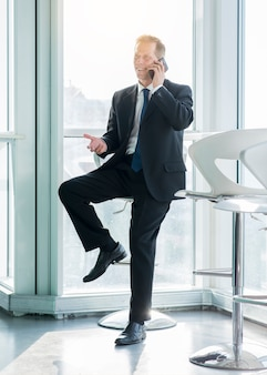 Lächelnder reifer geschäftsmann, der auf smartphone im büro spricht