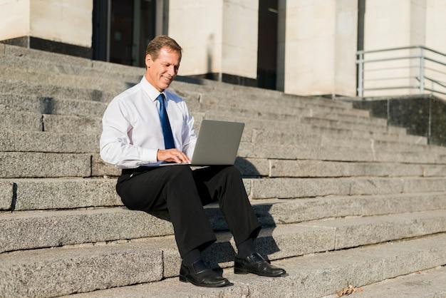 Lächelnder reifer geschäftsmann, der auf treppenhaus unter verwendung des laptops sitzt