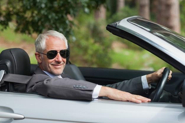 Lächelnder reifer geschäftsmann, der noblen cabriolet fährt
