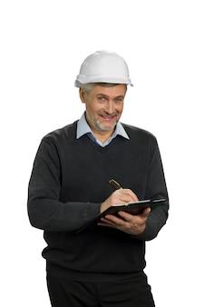 Lächelnder reifer ingenieur, weiß. leitender arbeiter im helm, der neues eigentum prüft