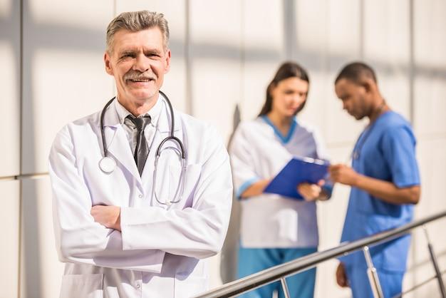 Lächelnder reifer männlicher doktor, der mit den armen gekreuzt steht.