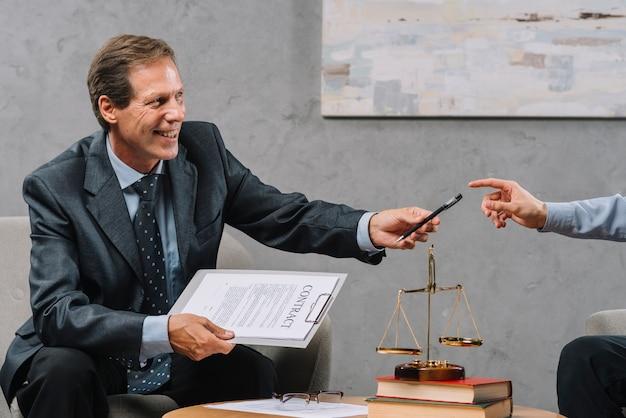 Lächelnder reifer männlicher rechtsanwalt, der in der hand vertrag in der hand gibt ihrem kunden stift hält