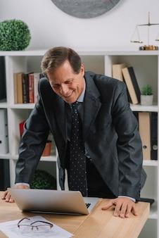 Lächelnder reifer männlicher rechtsanwalt, der laptop auf holztisch im gerichtssaal betrachtet