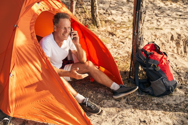 Lächelnder reifer mann geht nordic walking im wald und ruht sich beim camping aus, während er telefoniert