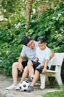 Lächelnder reifer mann und sein sohn, die auf bank im park ruhen, nachdem sie zusammen fußball gespielt haben