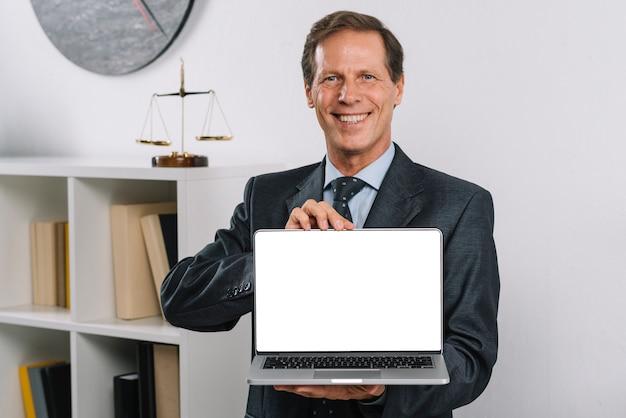 Lächelnder reifer rechtsanwalt, der den leeren laptopschirm steht im gerichtssaal zeigt