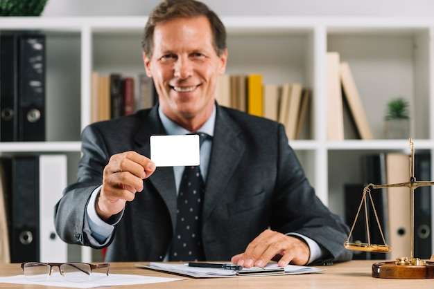 Lächelnder reifer rechtsanwalt, der die leere visitenkarte sitzt im gerichtssaal zeigt