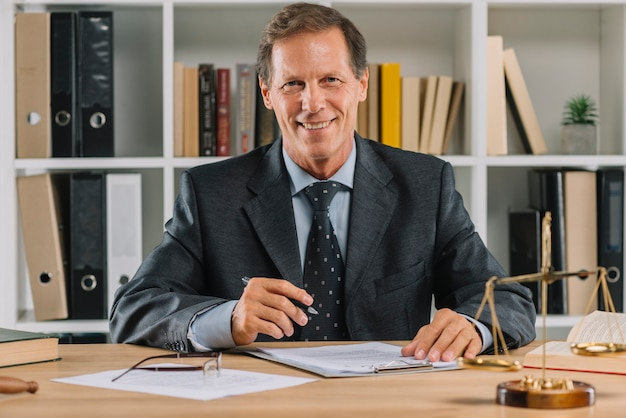 Lächelnder reifer rechtsanwalt, der im gerichtssaal arbeitet
