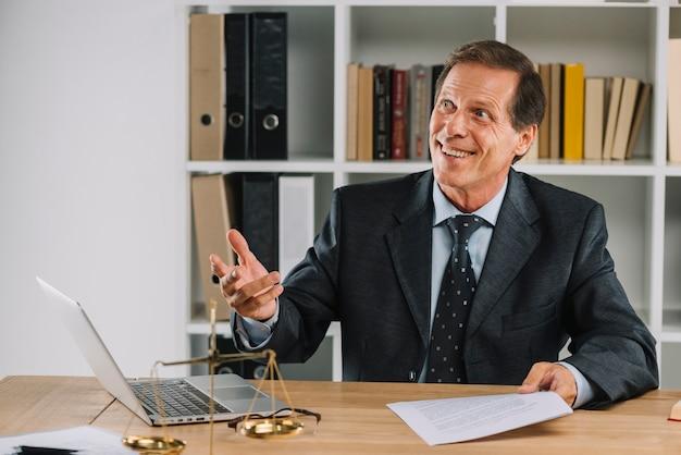Lächelnder reifer rechtsanwalt, der in der hand dokument am arbeitsplatz hält