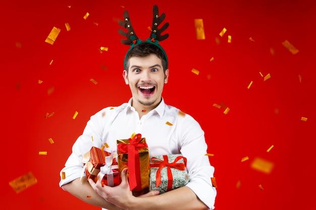 Lächelnder reizend hübscher hippie-mann-kerl des parteikonzeptes des neuen jahres glücklicher spaß, der die winterweihnachtsfeiertage tragen hirschhornhutholding feiert, stellt kastengeschenk goldene konfettis dar