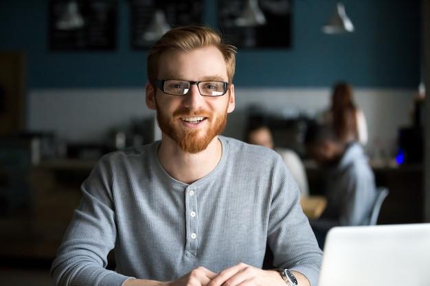 Lächelnder rothaarigemann mit dem laptop, der kamera im café betrachtet
