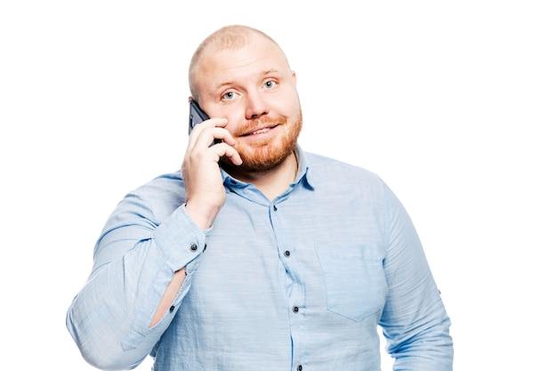 Lächelnder rothaarigemann mit einem bart spricht am telefon.