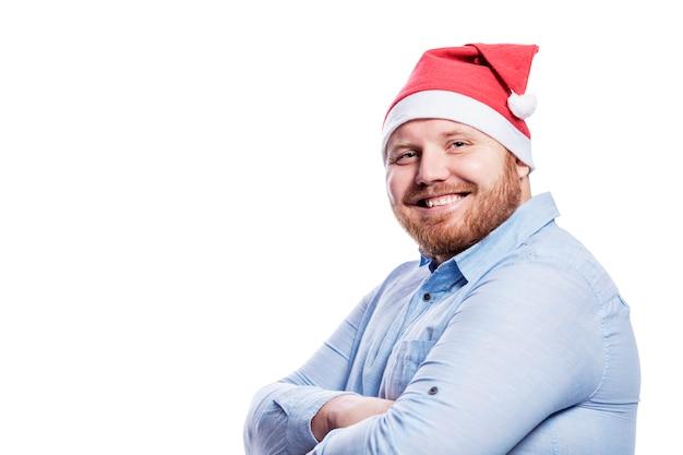Lächelnder rothaariger mann im weihnachtsmannhut. neujahrs- und weihnachtsfeier. isoliert. platz für text.