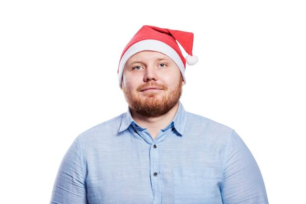 Lächelnder rothaariger mann im weihnachtsmannhut. neujahrs- und weihnachtsfeier. isoliert.