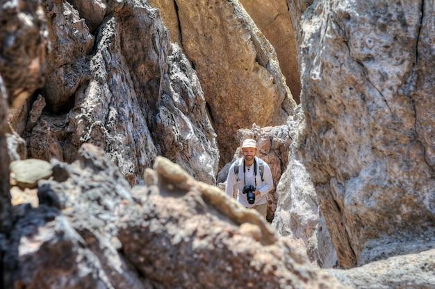 Lächelnder rucksacktourist mit kamera geht den weg zwischen felsen, hormuz island, hormozgan, iran.