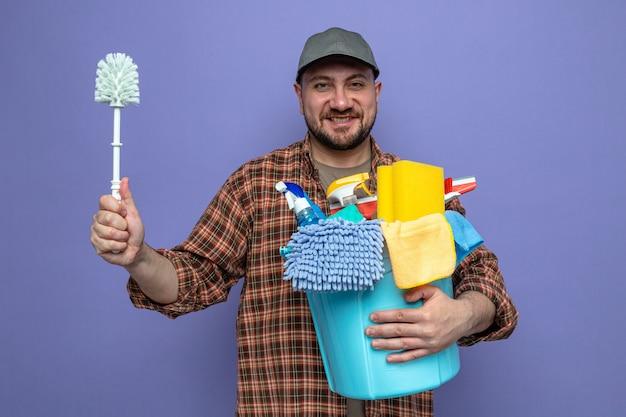 Lächelnder sauberer mann, der reinigungsgeräte und toilettenbürste hält