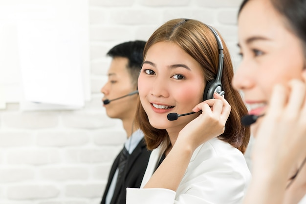 Lächelnder schöner asiatintelemarketing-kundendienstmitarbeiter in call-center